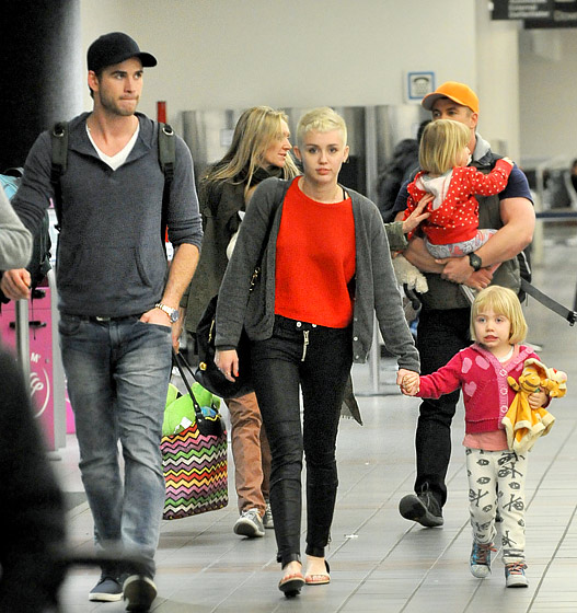 miley-cyrus-lax-aiport-isabel-marant-chai-sweater-textile-elizabeth-and-james-cooper-skinny-jeans-chloe-two-tone-ankle-strap-sandals-1